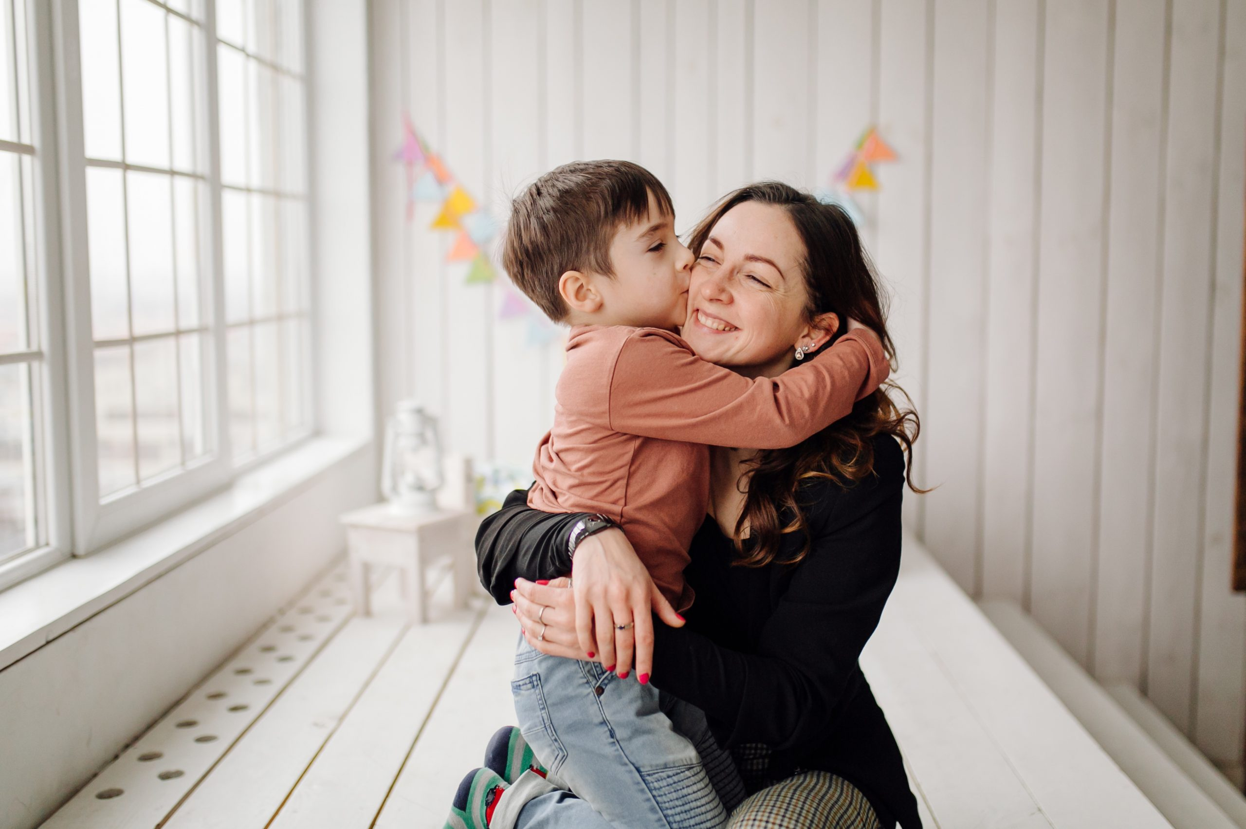 Mother and her son are posing in the studio and wearing casual clothes